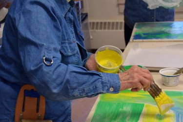 Colors and pigments are brushed on to a slab of clay.